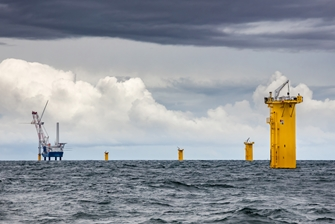stormy sea, yellow foundations of the wind turbines visible in the foreground, with a crane building a wind turbine in the background