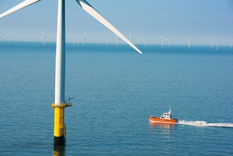 sunny view of the sea, a boat passing a wind turbine closely, with more wind turbines in the background