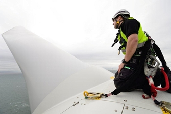 man wearing a harness attached to the wind turbine, inspecting one of the blades