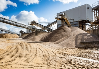 sunny view of the mining conveyor belts surrounded by piles of sand