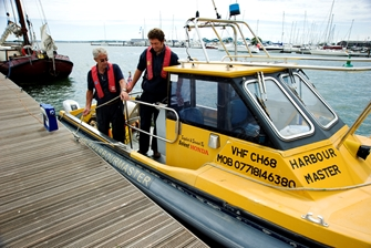 Two men getting out of a yellow boat with text harbour master on it