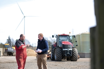 two men having a conversation on a farm, with a tractor close by and a wind turbine in the background