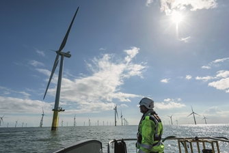 sunny view of the sea, a man on a boat is looking up at one of the many wind turbines visible on the horizon
