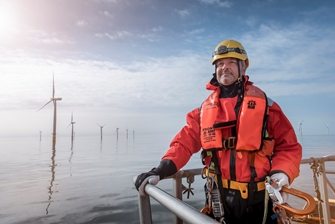 a man in protective clothing and harness is holding onto railing, posing for a picture with a row of wind turbines behind him