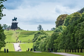 people walking through the park, up a hill to the monument of a rider