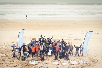a large group of people cheerfully posing for a photo next to 'beach clean' banners