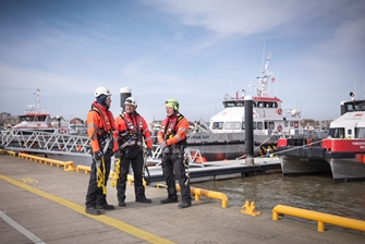 three men in protective clothing, wearing harness' are having a conversation in front of a bay full of boats