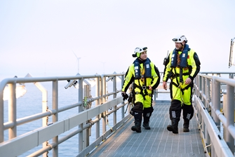 two men walking on a deck, dressed in high visibility clothing wearing helmets and a climbing harness