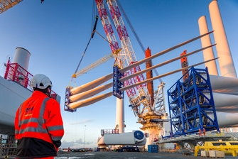 a person wearing a high visibility EDF jacket is overlooking a crane lifting three wind turbine blades