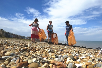 three people picking up rubbish from a pebbled beach