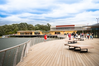 image of a wooden deck next to the water at Lakeside, families walking in the background