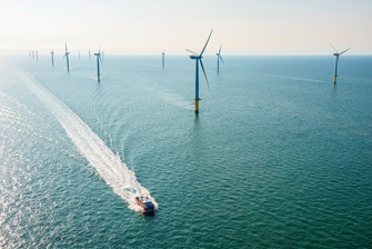 sunny view of the sea, a boat is passing a row of wind turbines, leaving trail waves behind it