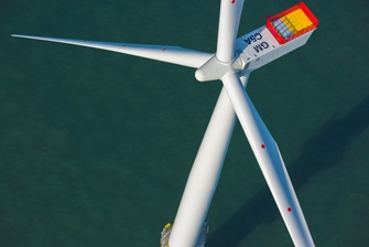 shot of the top of a wind turbine with a still sea below