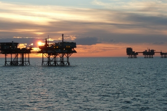 sunset, view onto working stations built on the seabed